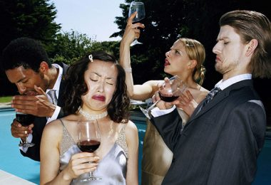 Four young people pulling faces whilst tasting red wine